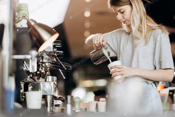 Eine gut aussehende schlanke Blondine mit langen Haaren, in lässigem Outfit gekleidet, ist das Kochen von Kaffee in einem modernen