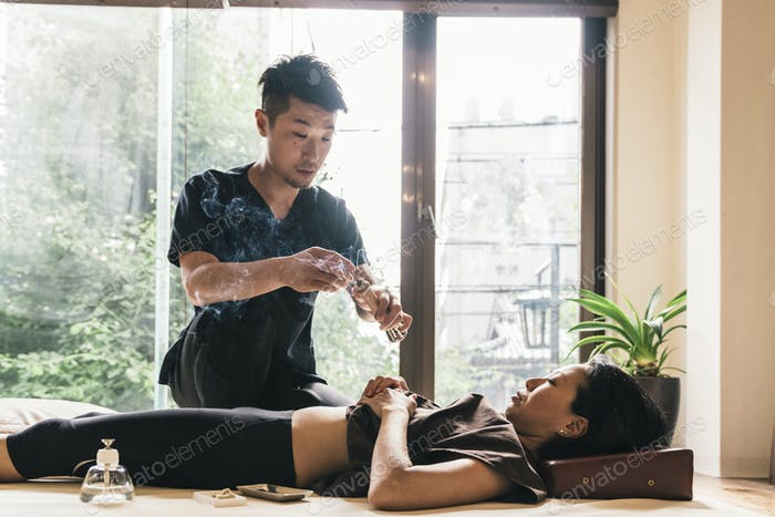 Therapist Giving Cupping Treatment To Young Asian Woman