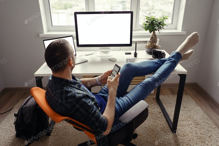 Modern man in home office relaxing with legs on the table