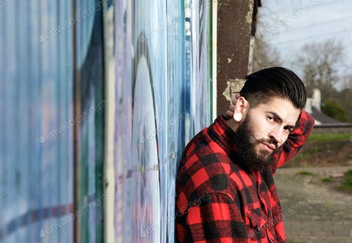Latin man with beard and piercings sitting outdoors
