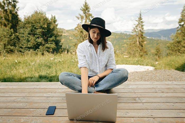 Hipster Mädchen mit Laptop sitzen auf Holzveranda