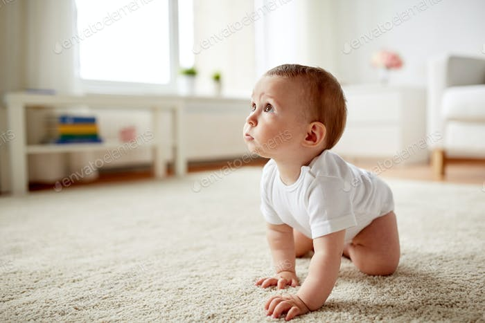 little baby in diaper crawling on floor at home