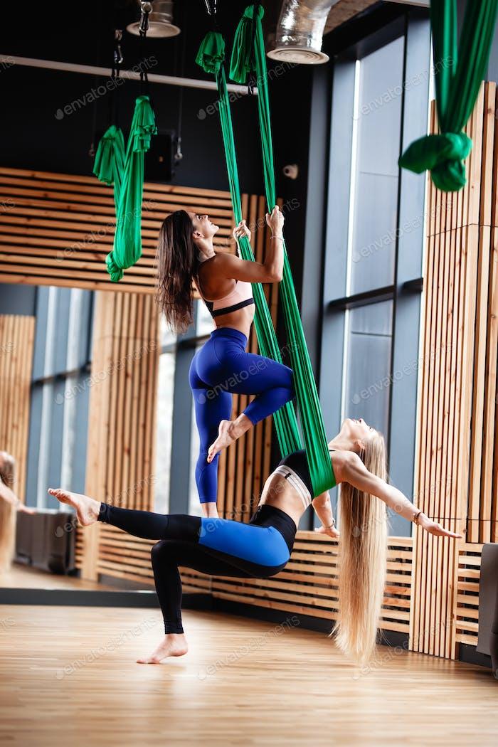 dos jóvenes atlético niñas morena y rubia están haciendo fitness en el verde aéreo de seda en el
