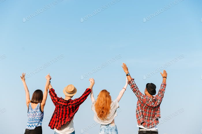 Back view of four young people holding raised hands