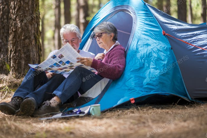 Adult mature retired couple enjouying the wild camping outdoor in the forest