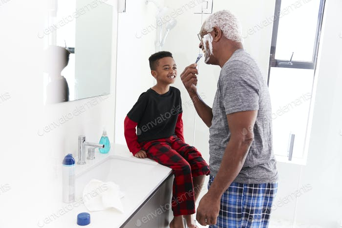 Grandfather Wearing Pajamas In Bathroom Shaving Whilst Grandson Watches