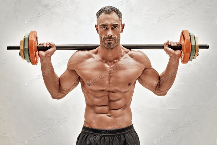 Close-up photo of a shirtless sportsman, flexing with a barbell in a bright studio