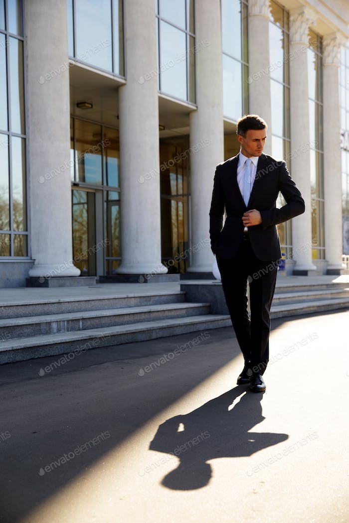 Confident businessman walking on the street