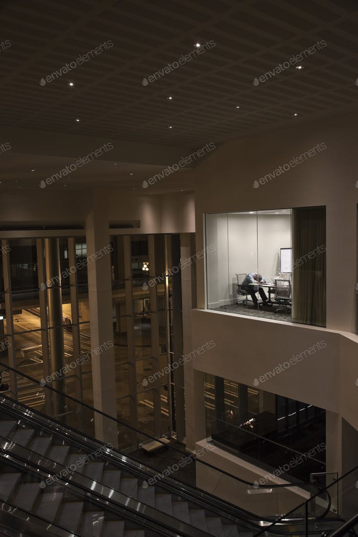 A view looking into a conference room at night  with a single businessman at a conference table.