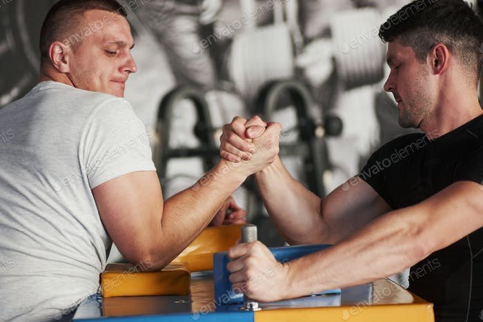 Conception of sport. Arm wrestling challenge between two men. Match on a special table
