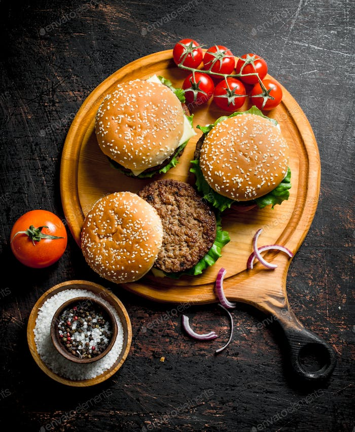 Burgers on a round cutting Board with spices and tomatoes.