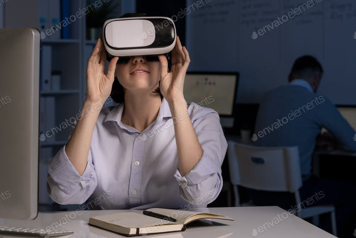 Young office worker with vr headset sitting by desk in front of computer