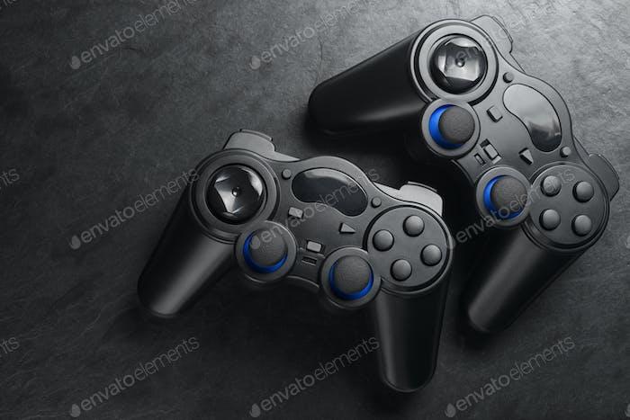 Black wireless gamepads or joysticks on black background.