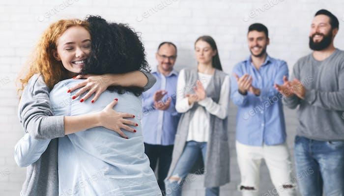Glückliche Menschen, die sich nach erfolgreichem Gruppentreffen in der Reha umarmen