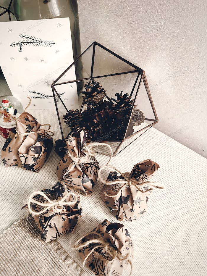 Rustic gifts on table with glass terrarium with pine cones