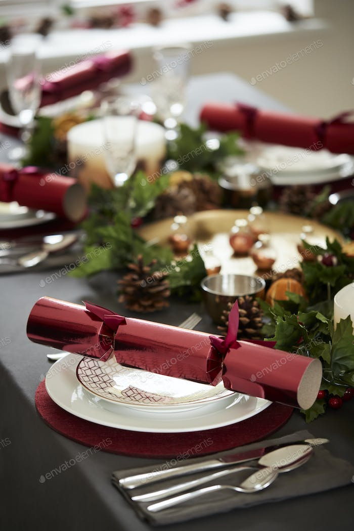 Close up of decorated Christmas table setting, with centrepiece and Christmas crackers