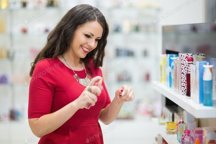 Happc beautiful woman testing perfumes