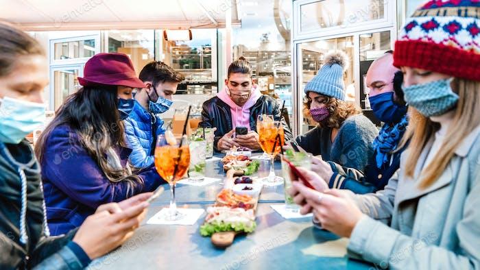 Milenial-Freunde nutzen mobile Smartphones an der Cocktailbar