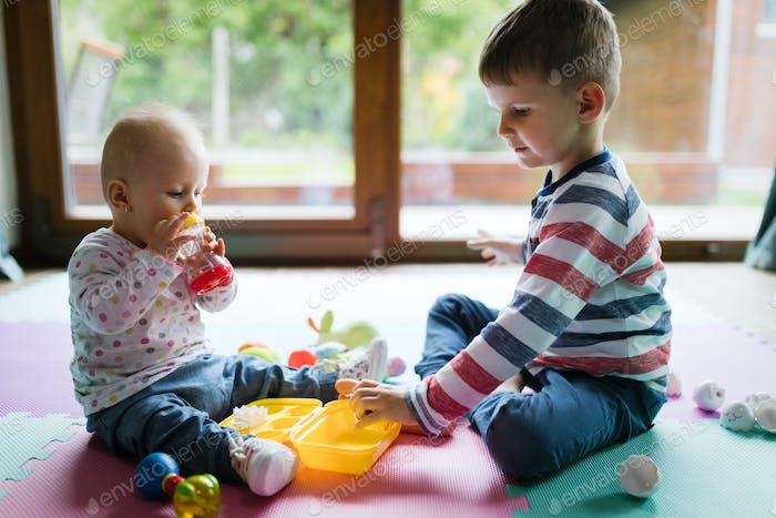 Niedliche kleine Kinder spielen beim Sitzen auf Teppich