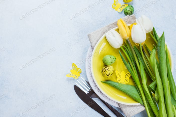 Easter table setting with tulips, quail eggs and cutlery. Spring Holidays Stone Blue background.