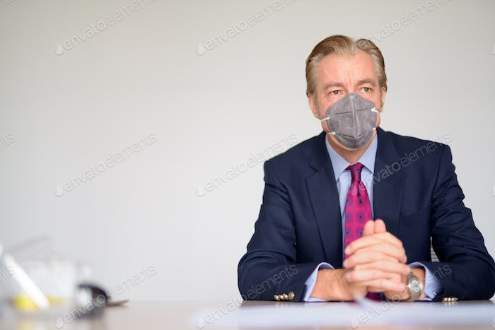 Mature businessman thinking with mask for protection from corona virus outbreak at work