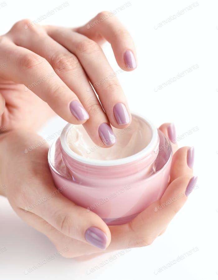 Hands of a woman with pink manicure with cream