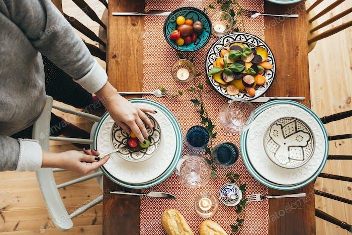 Niedriger Abschnitt der Frau arrangieren Essen in Schüssel auf gedeckten Tisch