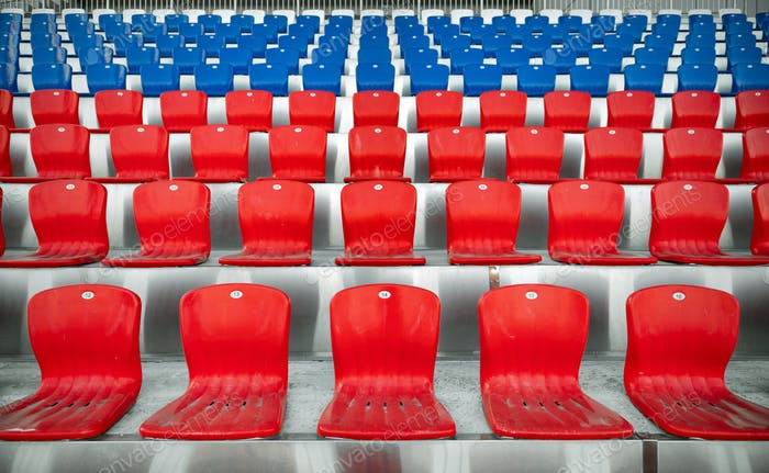 Empty red and blue rows of plastic seats in the stands of the stadium