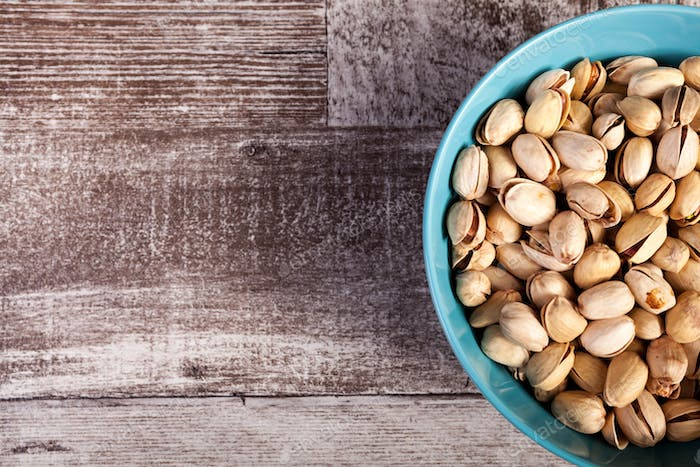 Over top view of Pistachios in blue bowl on wooden background in