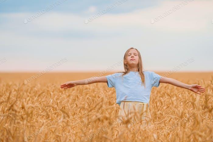 Glückliches kleines Mädchen zu Fuß in goldenen Weizenfeldern