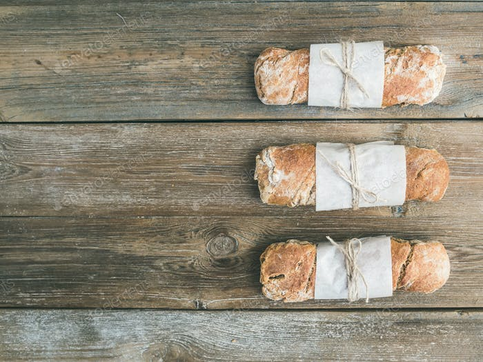 Freshly baked rustic  village bread (baguette) set on rough wood