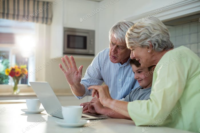 Grandson using laptop with grandparents