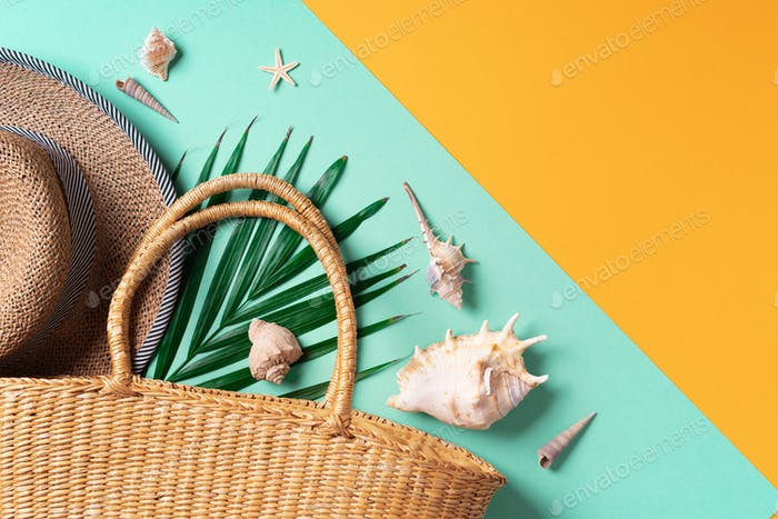 Summer fashion flat lay. Stylish straw bag, hat, palm leaves, shells on trendy yellow and green