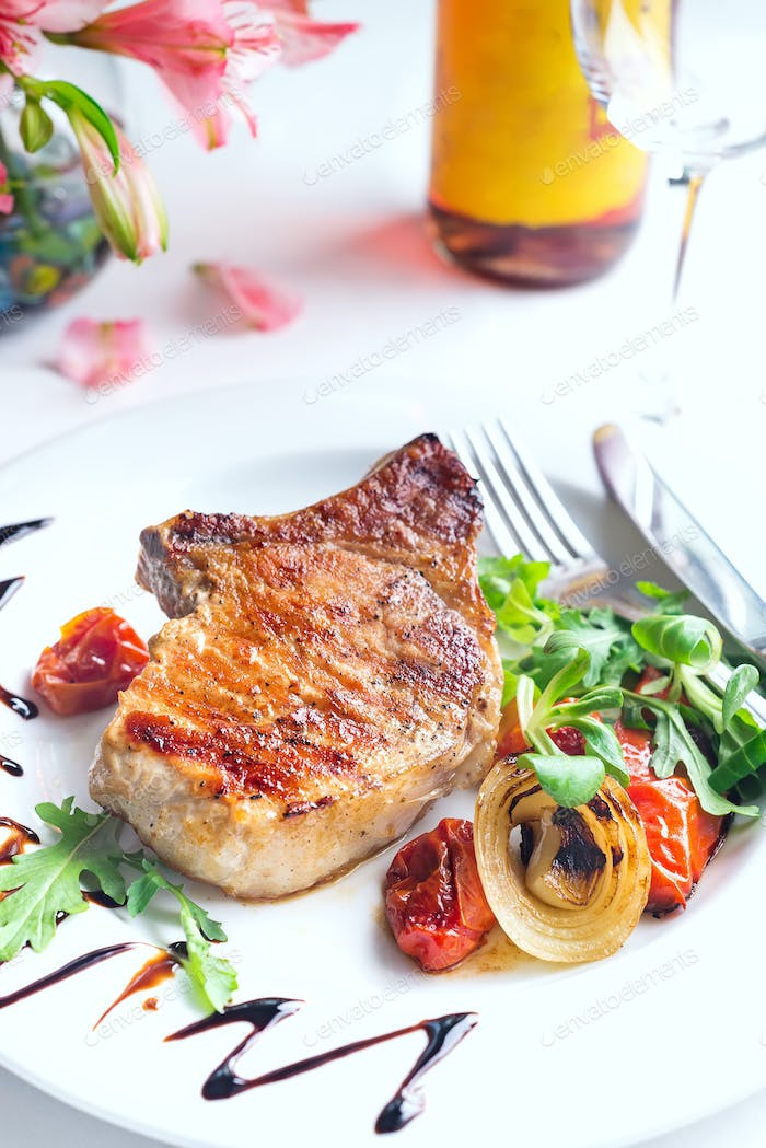 grilled beef steak and vegetables with wine and flowers on white background