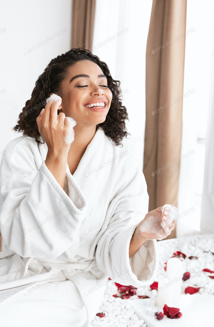 Emotional afro lady playing with foam, having spa at home