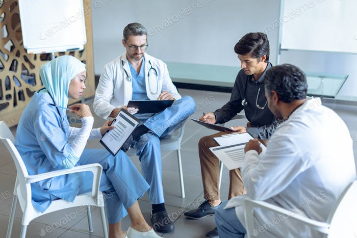 Diverse medical team with stethoscopes around the neck reading documents together in the hospital
