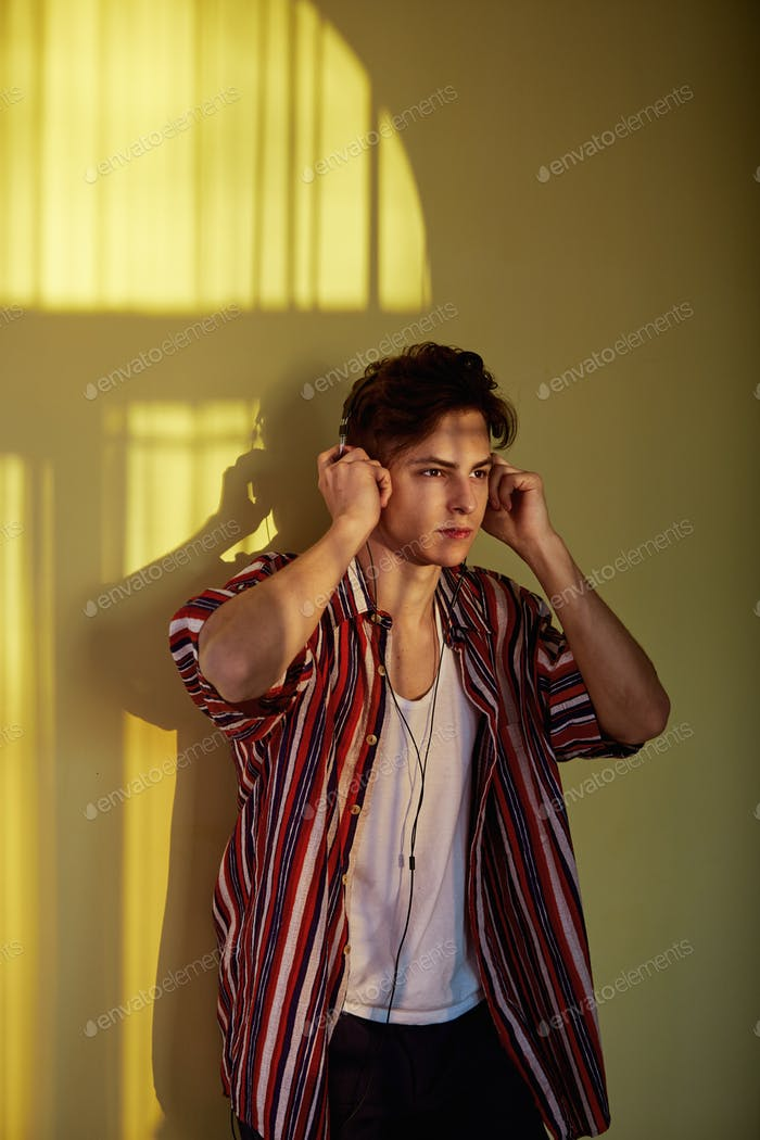 Dark-haired guy in a multi-colored striped shirt is leaning on the wall with a reflection of the