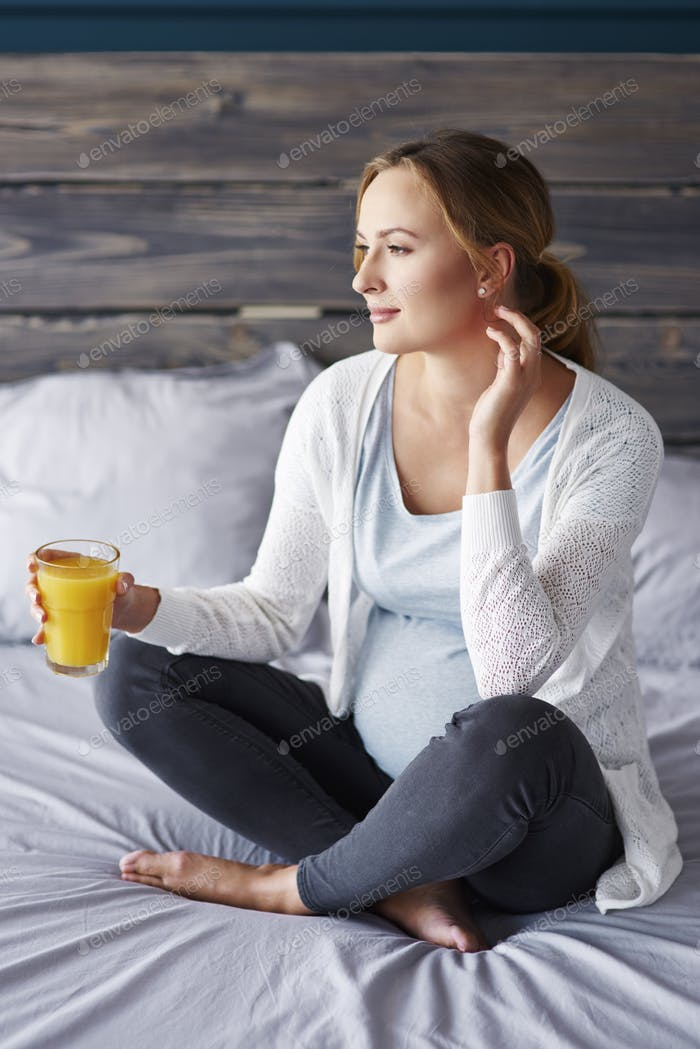 Pregnant woman with orange juice at bedroom