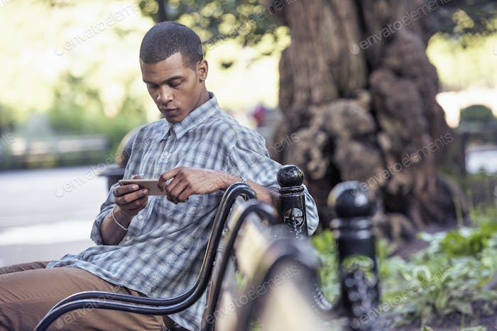 A man seated on a park bench using his smart phone