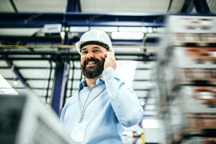 A portrait of an industrial man engineer with smartphone in a factory.