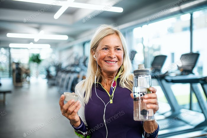 A senior woman with earphones and water bottle standing in gym.