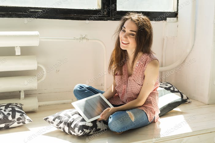 Young woman sitting on the wooden sill with tablet and pillows