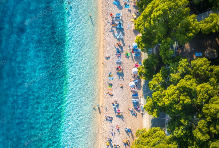 Aerial view of sandy beach with colorful umbrellas, blue sea sea