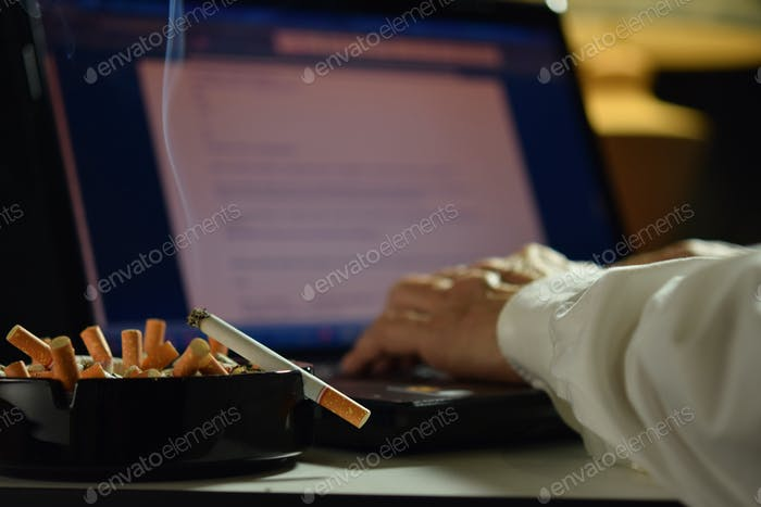 Man working on laptop computer with lit and smoking cigarette