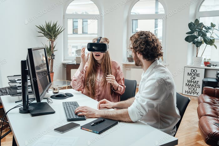 Woman with virtual reality glasses and guy typing on keyboard