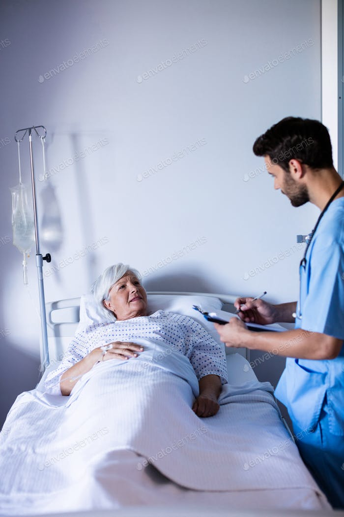 Male doctor discussing medical report with female senior patient on bed