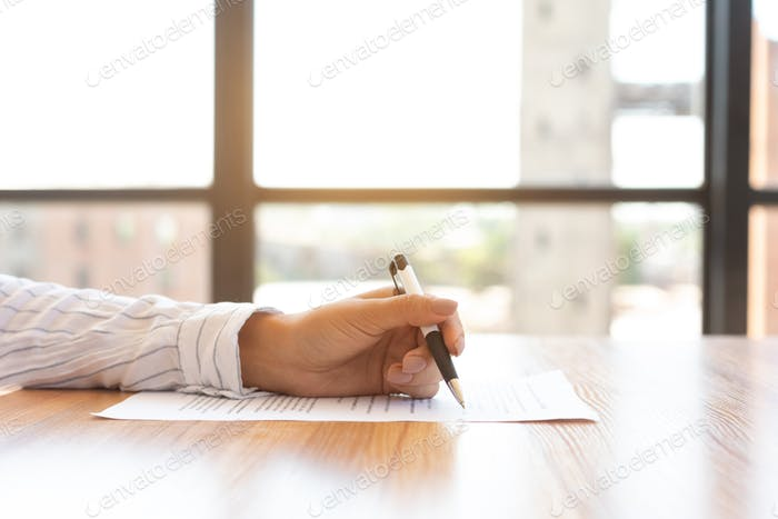 Businesswoman signing a document in modern office