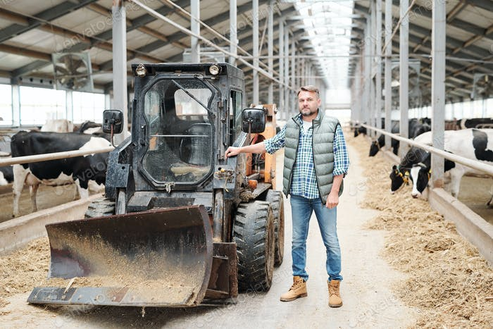 Mature confident worker of modern farmhouse standing by working equipment