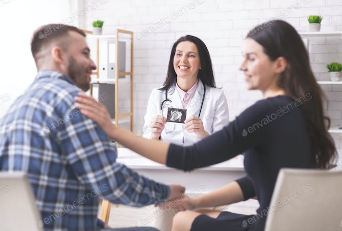 Happy couple enjoying pregnancy diagnosis in clinic