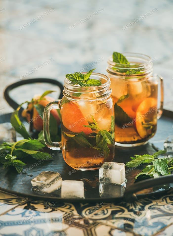 Summer refreshing cold peach ice tea with mint, copy space